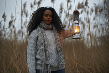 Woman Using Paraffin Lamp In Countryside