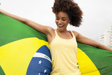 Young Woman Dancing With Brazilian Flag On Ipanema Beach, Rio De Janeiro, Brazil