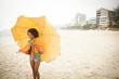 Young woman posing with umbrella on beach, Rio de Janeiro, Brazil