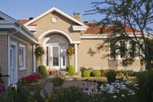 Beige Brick House Exterior With Front Door Portico And Flower Bed Garden
