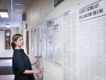 Female Worker Looking At Notice Board In Factory