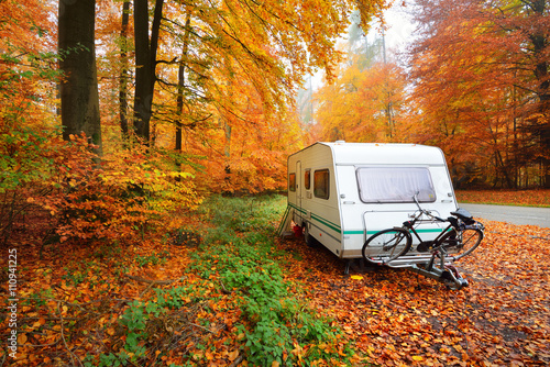 Fényképezés Caravan trailer with bicycle parked in a beautiful beech tree fo