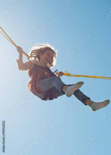 Little girl on bungee trampoline with cords. Place for text. Fotobehang