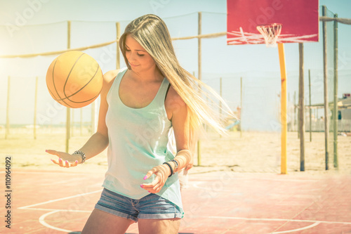 obraz dibond Sporty caucasian girl playing basketball