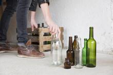Teenage Boy Placing Empty Bottles Into Wooden Crate In Garage