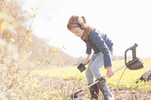 Girl Crouching With Spade And Metal Detector In Field