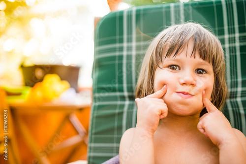 Valokuva  Cute little girl outside in garden holding her cheeks