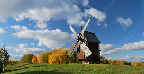 Old wooden windmill is in an autumn landscape