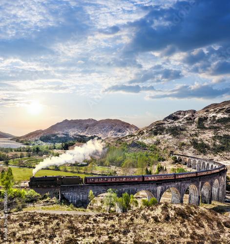 Fototapeta Glenfinnan Railway Viaduct in Scotland with the Jacobite steam train against sunset over lake obraz na płótnie