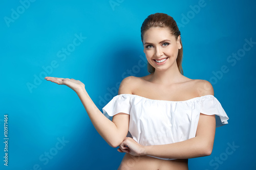 Valokuva  Young blond woman showing empty copy space on the open hand for text on blue bac