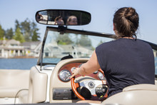Rear View Of Young Woman Driving Motor Boat, Lake Oswego, Oregon, USA