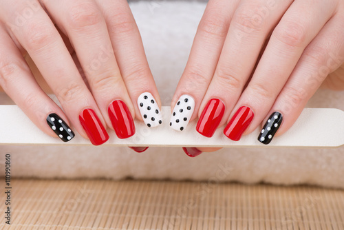 Staande foto Manicure Manicure - Beauty treatment photo of nice manicured woman fingernails. Very nice feminine nail art with nice red, white and black nail polish.