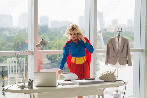 Photo  Powerful superwoman talking on phone and working with documents  in office