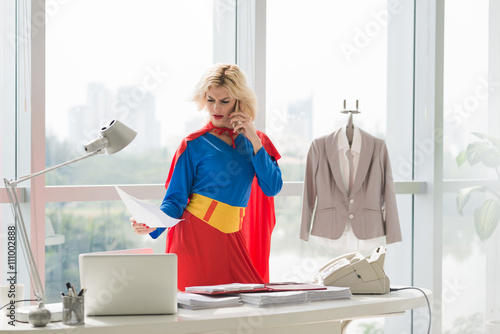 Photo  Angry superwoman reading document when negotiating by phone