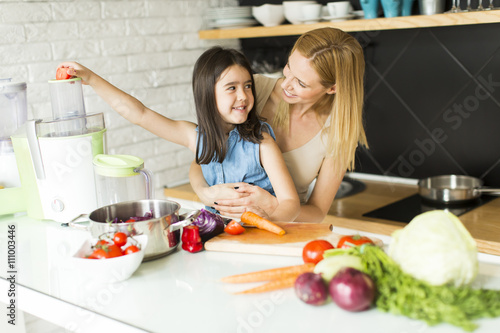 Photo  Mother and daughter in the kitchen make juice