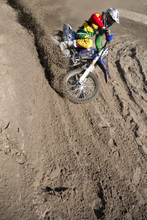 Young Male Motocross Rider Racing Down Mud Hill