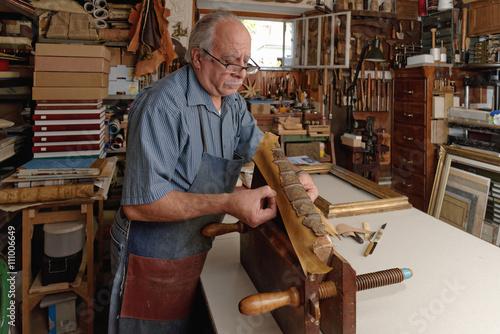 Senior man repairing fragile antique book spine in traditional bookbinding workshop