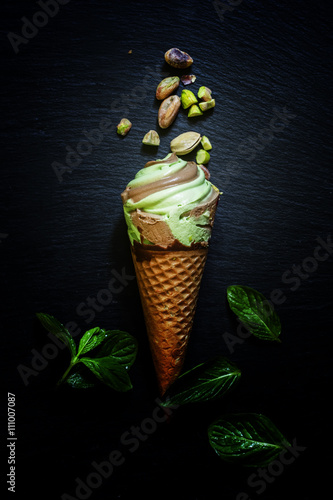 Photo  Mint pistachio ice cream with chocolate in waffle cone, scattere