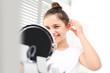 Niewidoczny aparat słuchowy. Wesoła dziewczynka zakłada aparat słuchowy przeglądając się w lusterku