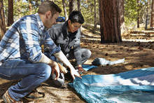 Two Young Men Preparing To Camp In Forest, Los Angeles, California, USA