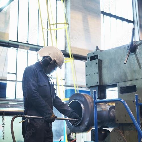 Worker polishing inside of tube in engineering factory