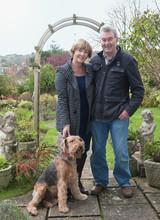 Portrait Of Senior Couple With Dog In Garden