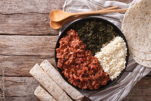 Ethiopian kitfo with herbs and cheese ayibe close-up. Horizontal top view