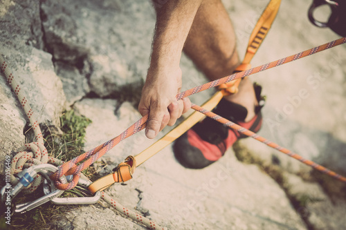 Poster Climber securing a rope on a stone wall