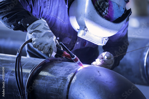 Fototapeta Worker welding metal piping using tig welder obraz