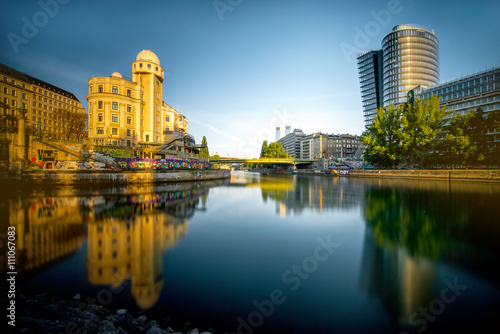 Garden Poster Vienna Vienna cityscape with modern Uniqa and Urania tower on the water channel in the morning. Long exposure image technic with glossy water and reflection