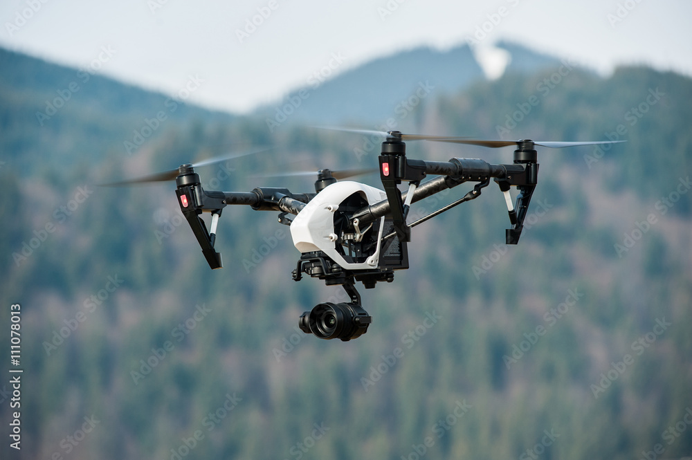 Fototapeta drone with high resolution digital camera/White drone with digital camera flying in sky over mountain