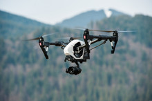Drone With High Resolution Digital Camera/White Drone With Digital Camera Flying In Sky Over Mountain