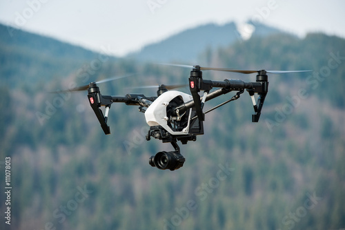 Fototapeta drone with high resolution digital camera/White drone with digital camera flying in sky over mountain obraz
