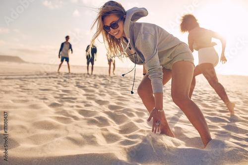 Plakat Młoda kobieta bieg rasa z przyjaciółmi przy plażą