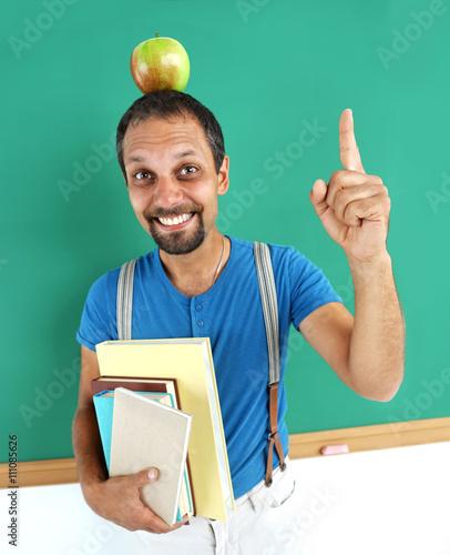 Fotografía  Amusing teacher literature with an apple on her head