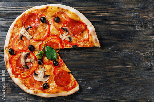 Spoed Foto op Canvas Pizzeria Top view of Italian rustic PIZZA mushrooms, basil, tomato, olives and cheese. Cut off a piece and pushed. Dark wooden table background. Look as Prosciutto, Capricciosa, Funghi, Cotto PIZZA.