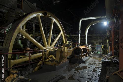 Tuinposter Oude verlaten gebouwen Giant flywheel in old colonial factory