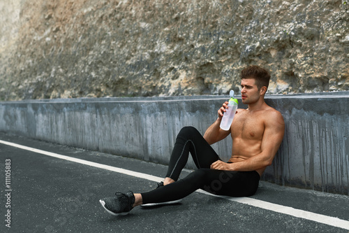 Fototapety, obrazy: Tired Exhausted Athletic Man With Muscular Body Drinking Water, Resting After Running Workout. Thirsty Male Drinking Refreshing Drink After Outdoor Training On Hot Summer Day. Sports, Fitness Concept