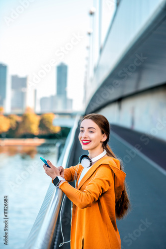 Photo  Young sport woman in yellow sweater using smart phone on the modern bridge with skyscrapers on the background