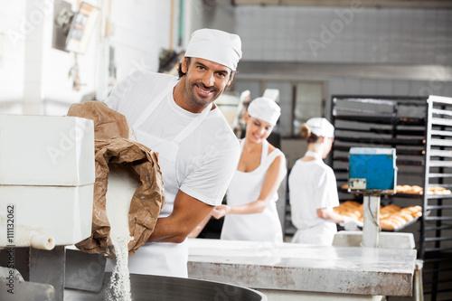 Staande foto Bakkerij Smiling Male Baker Pouring Flour In Kneading Machine