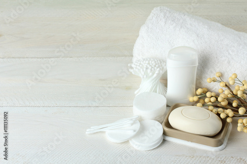 Fotografía  personal hygiene items with decorative sprigs on a white wooden background