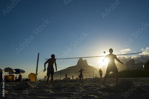 Plakat Sylwetki Brazylijczyków grać futevolei (footvolley) na tle zachodu słońca z Dois Irmaos Two Brothers Mountain na plaży Ipanema, Rio de Janeiro Brazylia