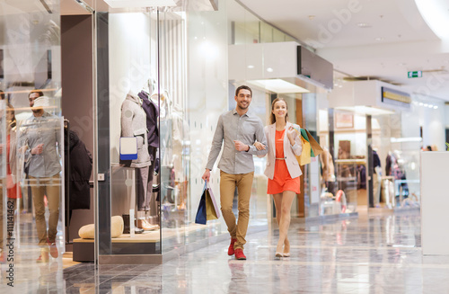 Photo happy young couple with shopping bags in mall