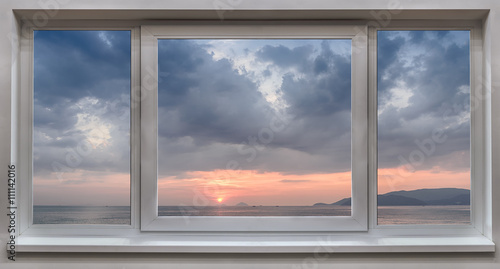 Cuadros en Lienzo A window with the panoramic views of the sea and the beautiful sunrise