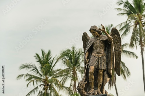 Archangel Michael Sculpture, The archangel isolated on isolated against a blue sky at sunlight Fotobehang