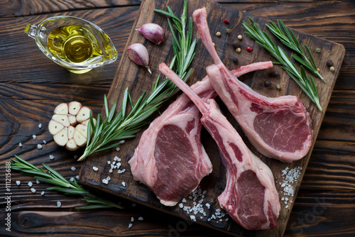 Photo  Raw fresh seasoned lamb chops in a rustic wooden setting