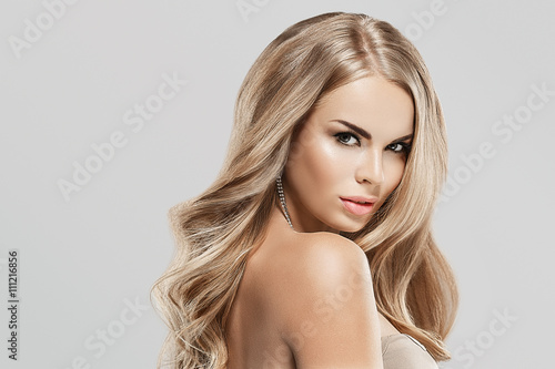 Woman with blonde hair. Studio shot. Gray background. Poster