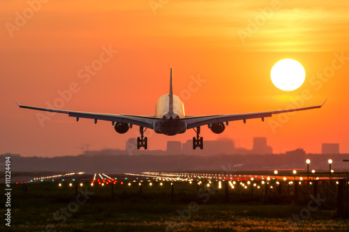 Photo Passenger plane is landing during a wonderful sunrise.