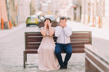 Young Woman And Man Sitting On Bench Closing Eyes With Palms