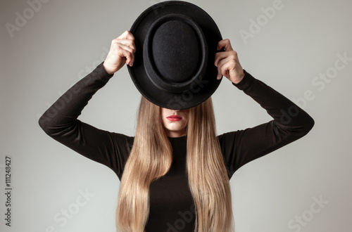 Beautiful long straight blond hair with a black hat in the studio Plakát